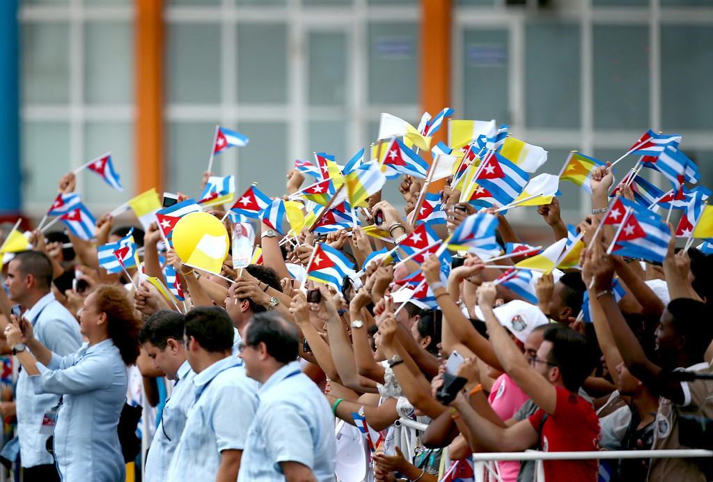 . Youngsters wave Cuban and Vatican flags during the arrival of Pope Francis at Jose Marti International Airport on September 19, 2015 in Havana, Cuba. Pope Francis is at the beginning of a three day visit to Cuba where he will meet President Raul Castro and hold Mass in Revolution Square before travelling to Holguin, Santiago de Cuba and El Cobre then onwards to the United States.  (Photo by Carl Court/Getty Images)