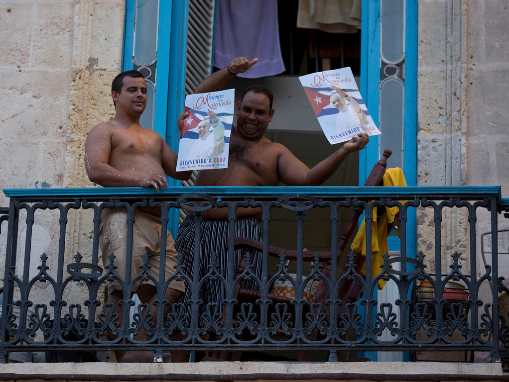. Two men hold posters of Pope Francis as they react to the camera in Havana, Cuba, Friday, Sept. 18, 2015. Francis will visit Cuba from Sept. 19-22, before arriving in the United States, making him the third pontiff to visit the island nation. (AP Photo/Alessandra Tarantino)