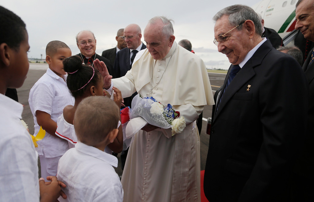 . Pope Francis blesses a girl as Cuba\'s President Raul Castro looks on after landing at the airport in Havana, Cuba, Saturday, Sept. 19, 2015. Pope Francis began his 10-day trip to Cuba and the United States, embarking on his first trip to the onetime Cold War foes after helping to nudge forward their historic rapprochement.(Ismael Francisco/Cubadebate Via AP)