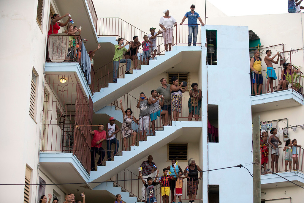 . People watch from their apartment building as Pope Francis approaches in his popemobile as he travels from the airport to Havana, Cuba, Saturday, Sept. 19, 2015. Pope Francis began his 10-day trip to Cuba and the United States, embarking on his first trip to the onetime Cold War foes after helping to nudge forward their historic rapprochement. (Ismael Francisco/Cubadebate Via AP)