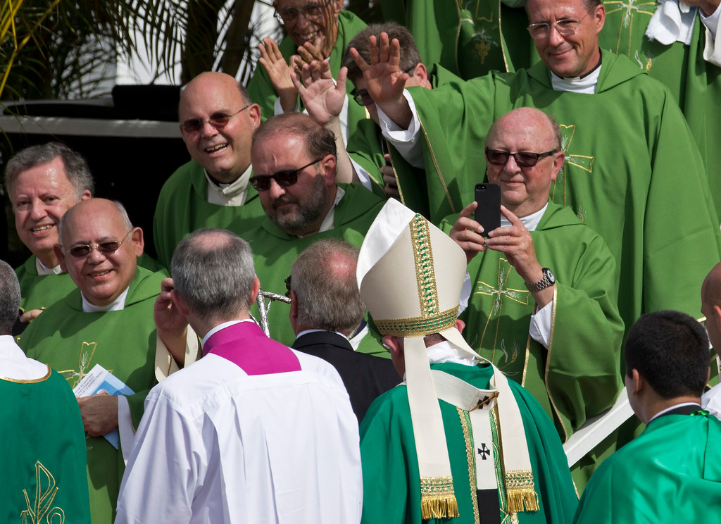 . Clergy wave to and take pictures of Pope Francis after he celebrated Mass at Revolution Plaza in Havana, Cuba, Sunday, Sept. 20, 2015. Pope Francis opened his first full day in Cuba on Sunday with what normally would be the culminating highlight of a papal visit: Mass before hundreds of thousands of people in Havana\'s Revolution Plaza. (AP Photo/Ramon Espinosa)