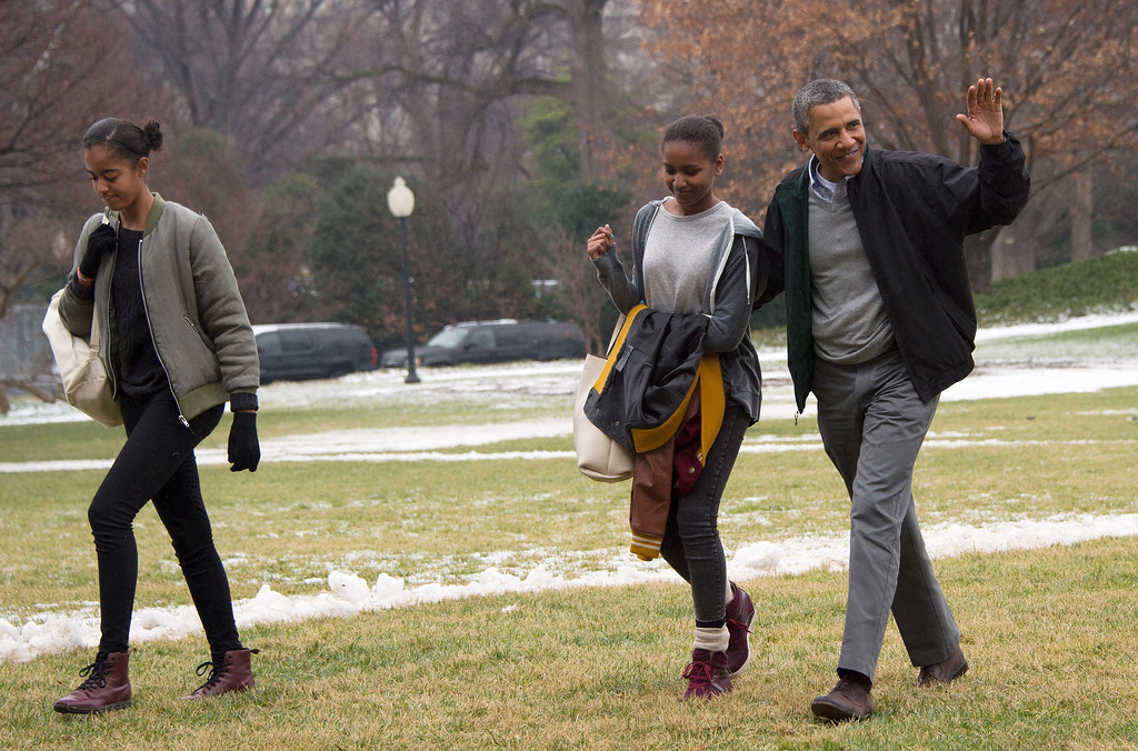 ". US President Barack Obama (R) waves as he walks with his daughters Sasha (C) and Malia as they arrive back at the White House in Washington, DC, January 5, 2014. Obama late Saturday ended his vacation in sunny Hawaii and boarded Air Force One for a flight back home to chilly Washington. Obama left Honolulu\'s Joint Base Pearl Harbor-Hickam just before 9:00 pm (0700 GMT Sunday) with his daughters, who likely have school on Monday, but not Michelle. ""As part of her birthday gift from the president, the First Lady will remain in Hawaii to spend time with friends ahead of her upcoming 50th birthday,\"" a brief White House statement said. Michelle Obama\'s birthday is on January 17.      (JIM WATSON/AFP/Getty Images)"