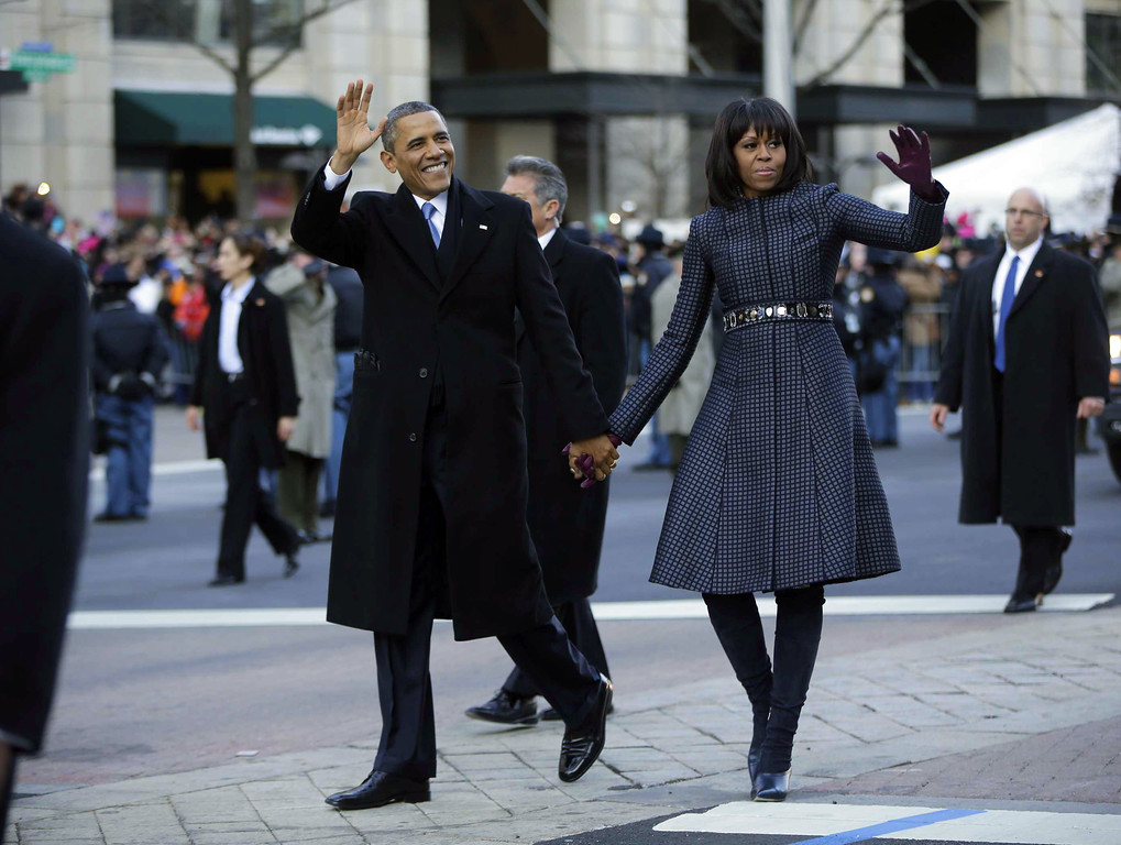 . President Barack Obama and first lady Michelle Obama walk down Pennsylvania Avenue during the 57th Presidential Inauguration parade Monday, Jan. 21, 2013, in Washington. (AP Photo/Charles Dharapak)