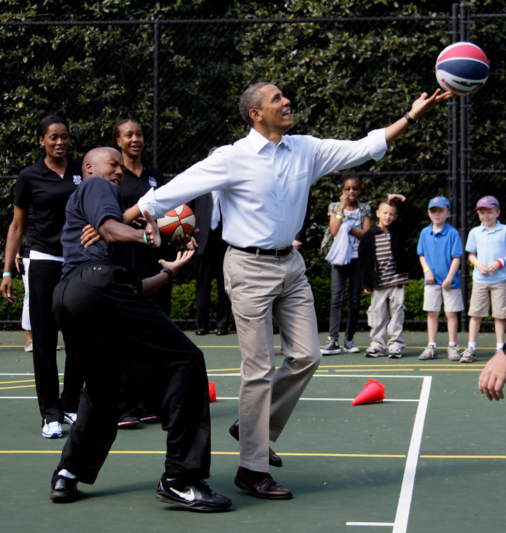 . President Barack Obama plays basketball with former NBA basketball player Bruce Bowen during the annual White House Easter Egg Roll, Monday, April 9, 2012, at the White House in Washington. (AP Photo/Carolyn Kaster)
