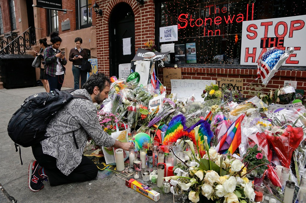 . FILE - In this June 16, 2016 file photo, a man lights candles on a memorial outside the Stonewall Inn for victims of the Orlando Shooting, in New York. President Barack Obama is designating the Stonewall Inn in New York a national monument, the first to honor gay rights. AP (AP Photo/Julie Jacobson, File)