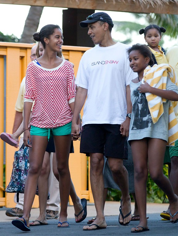 . President Barack Obama holding hands with his daughters Malia, left, and Sasha, right, leave Sea Life Park, a marine wildlife park, with family friends, Tuesday, Dec. 27, 2011, in Waimanalo, Hawaii. (AP Photo/Carolyn Kaster)