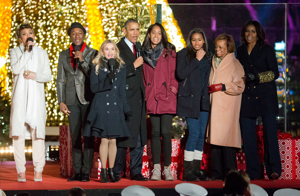 . President Barack Obama, center, with from left to right, singer Andra Day, Aloe Blacc, actress Reese Witherspoon, daughters Malia and Sasha, mother-in-law Marian Robinson and first lady Michelle Obama, sing onstage during the National Christmas Tree Lighting ceremony at the Ellipse in Washington, Thursday, Dec. 3, 2015. (AP Photo/Pablo Martinez Monsivais)