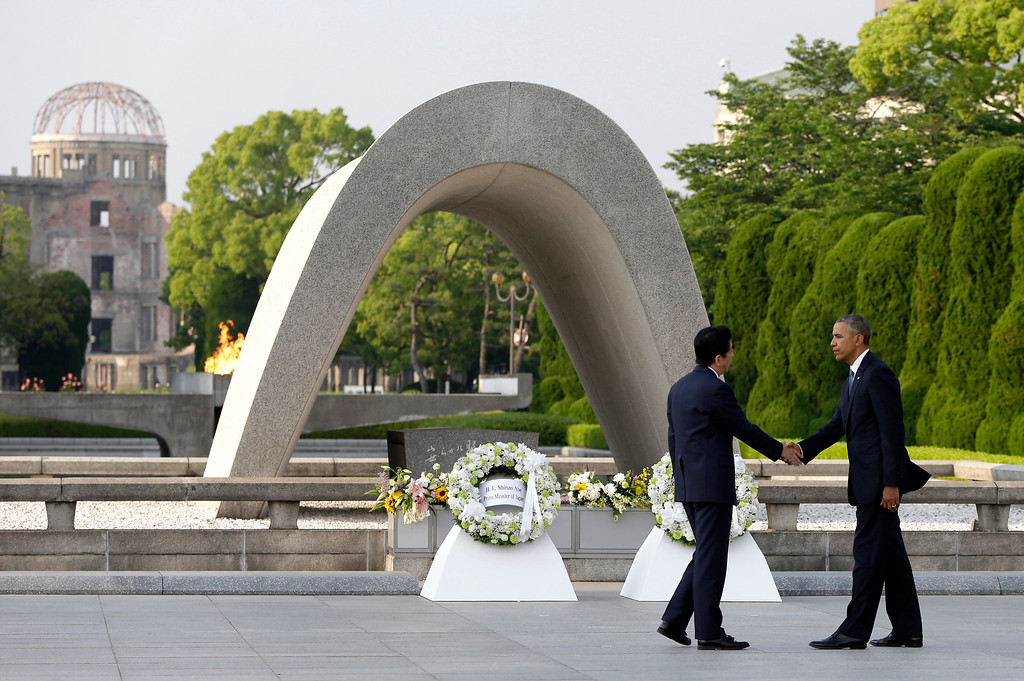 . FILE - In this May 27, 2016 file photo, U.S. President Barack Obama, right, shakes hands with Japanese Prime Minister Shinzo Abe at Hiroshima Peace Memorial Park in Hiroshima, western Japan, as Obama became the first sitting U.S. president to visit the site of the world\'s first atomic bomb attack. Abe said Monday, Dec. 5, he will visit Pearl Harbor with Obama at the end of this month, becoming the first leader of his country to go to the USS Arizona Memorial in the harbor in Hawaii that Japan attacked in 1941, propelling the United States into World War II. Atomic Bomb Dome is seen in the background. (AP Photo/Carolyn Kaster, File)