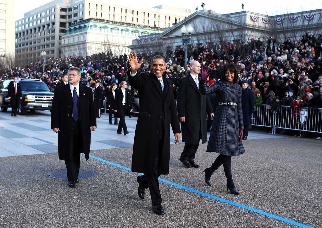 . President Barack Obama and first lady Michelle Obama wave as they walk down Pennsylvania Avenue in Washington, Monday, Jan. 21, 2013, during the Inaugural Parade after his ceremonial swearing-in on Capitol Hill during the 57th Presidential Inauguration. (AP Photo/The New York Times, Doug Mills, Pool)