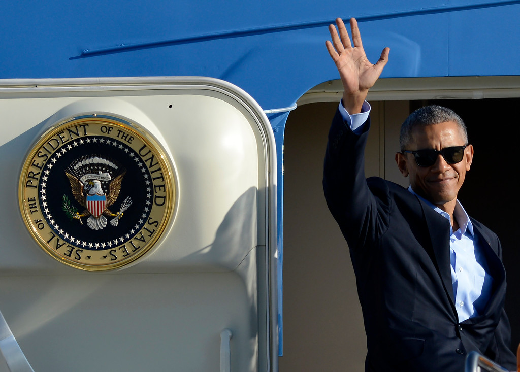 . FILE - In this Oct. 9, 2016 file photo, President Barack Obama, wearing sunglasses, waves while boarding Air Force One before leaving O\'Hare International Airport in Chicago. From his campaign fist bump to his theatrical mic drop at the last White House correspondents� dinner, Barack Obama ruled as America�s pop culture president. His two terms played out like a running chronicle of the trends of our times: slow-jamming the news with Jimmy Fallon, reading mean tweets with Jimmy Kimmel, filling out his NCAA basketball bracket on ESPN, cruising with Jerry Seinfeld on �Comedians in Cars Getting Coffee.�  (AP Photo/Paul Beaty, File)