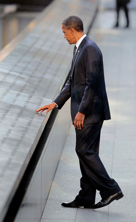 . President Barack Obama touches names of the 9/11 victims as he visits the North Memorial Pond at the National Sept. 11th Memorial ceremony Sunday, Sept., 11, 2011 in New York. (AP Photo/Pablo Martinez Monsivais)