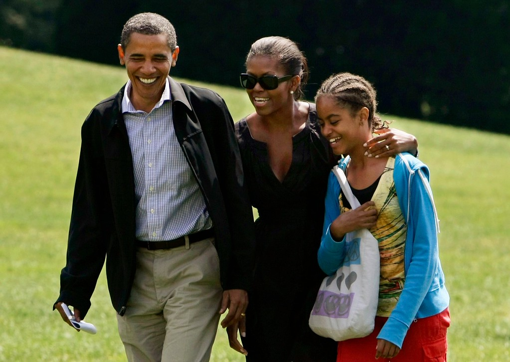 . President Barack Obama and first lady Michelle Obama, with daughter Malia Obama, return to the White House after five days at Camp David in Washington, Sunday, Sept. 6, 2009.  (AP Photo/J. Scott Applewhite)