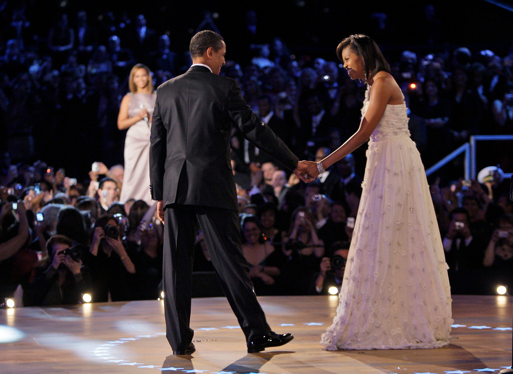 . President Barack Obama, left, and first lady Michelle Obama begin their first dance together at the Neighborhood Inaugural Ballin Washington, Tuesday, Jan. 20, 2009.  At rear is singer Beyonce. (AP Photo/Elise Amendola)