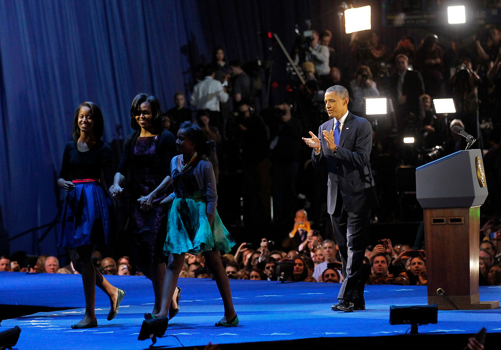 . President Barack Obama, right, applauds his wife Michelle and daughters Sasha and Malia as they leave the stage before speaking at his election night party, Wednesday, Nov. 7, 2012, in Chicago. President Obama defeated Republican challenger former Massachusetts Gov. Mitt Romney.  (AP Photo/Jerome Delay)