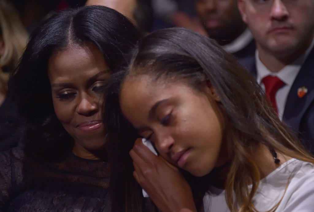 . US  first lady Michelle Obama (L) holds her daughter Malia as US President Barack Obama speaks during his farewell address in Chicago, Illinois on January 10, 2017. Barack Obama closes the book on his presidency, with a farewell speech in Chicago that will try to lift supporters shaken by Donald Trump\'s shock election. (NICHOLAS KAMM/AFP/Getty Images)