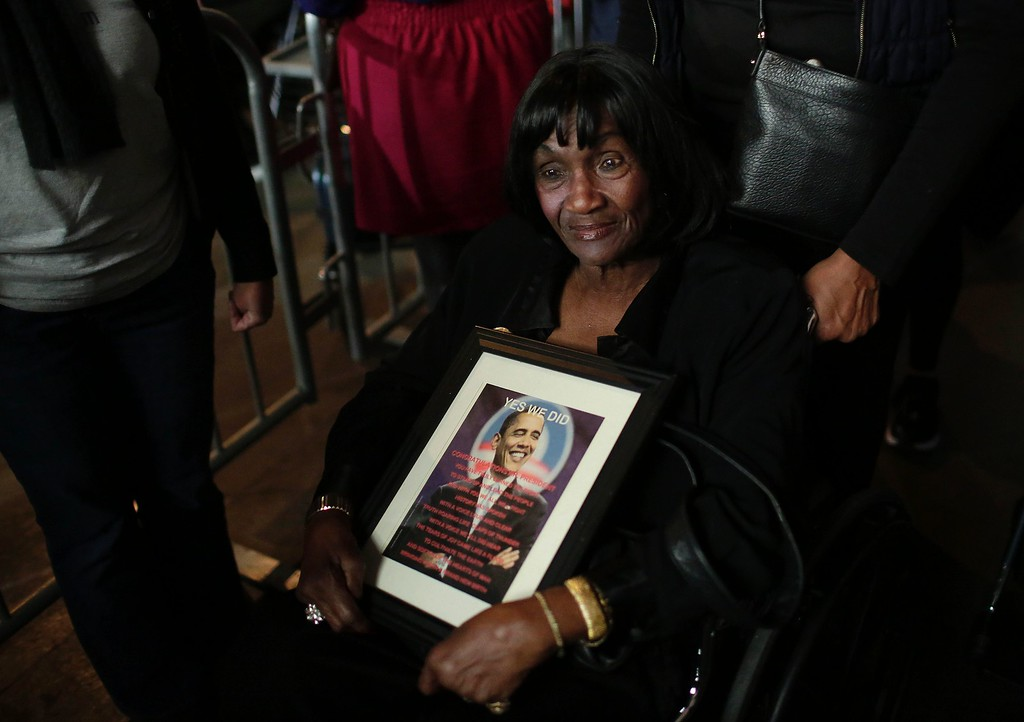 . A woman holds a photo of President Barack Obama before he gives his farewell address in Chicago, Illinois on January 10, 2017. Barack Obama closes the book on his presidency, with a farewell speech in Chicago that will try to lift supporters shaken by Donald Trump\'s shock election. (JOSHUA LOTT/AFP/Getty Images)