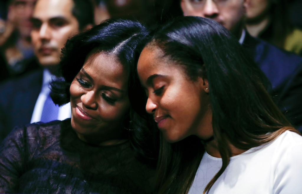 . First lady Michelle Obama and daughter Malia lean into one another as they listen to President Barack Obama speak during his farewell address at McCormick Place in Chicago, Tuesday, Jan. 10, 2017. (AP Photo/Pablo Martinez Monsivais)