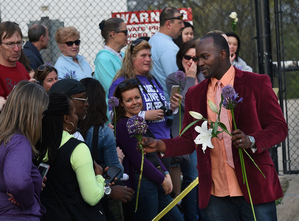 . A staff member hands out flowers to fans from a memorial service that was held inside the Paisley Park compound of music legend Prince, who died suddenly at the age of 57, in Minneapolis, Minnesota, on April 23, 2016. Family, friends and musicians attended the service after the remains of Prince were cremated before being placed in a private location. (MARK RALSTON/AFP/Getty Images)