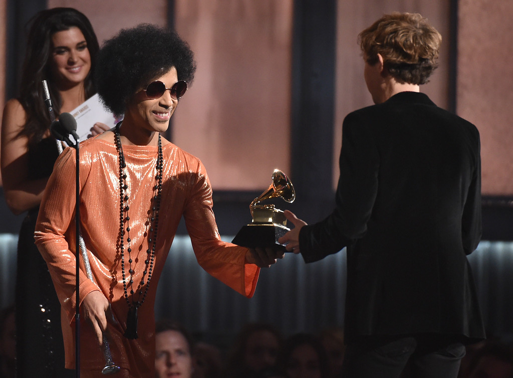 . Prince, left, presents Beck with the award for album of the year for �Morning Phase�at the 57th annual Grammy Awards on Sunday, Feb. 8, 2015, in Los Angeles. (Photo by John Shearer/Invision/AP)