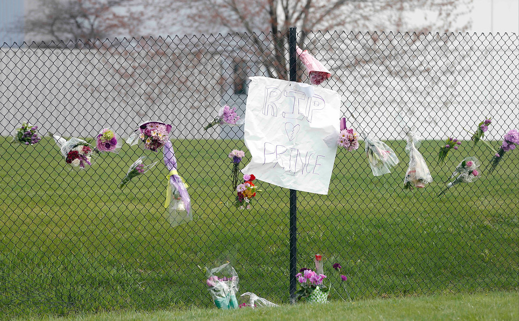 . Flowers and a sign appear on the fence at Paisley Park Studios, the home and studio of singer Prince, Thursday, April 21, 2016 in Chanhassen, Minn. Prince died at the home, Thursday, at the age of 57.  (AP Photo/Jim Mone)
