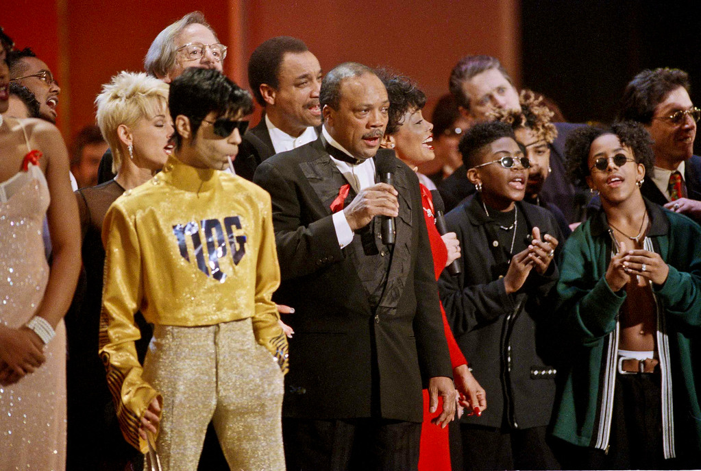 """. As dozens of singers perform \""""We Are The World\"""" on the 10th anniversary of the African famine relief anthem, the artist formerly  known as Prince, left, stands sucking on a lollipop next to Quincy Jones, at the American Music Awards in Los Angeles, January 30, 1995. ( AP Photo/ Reed Saxon )"""