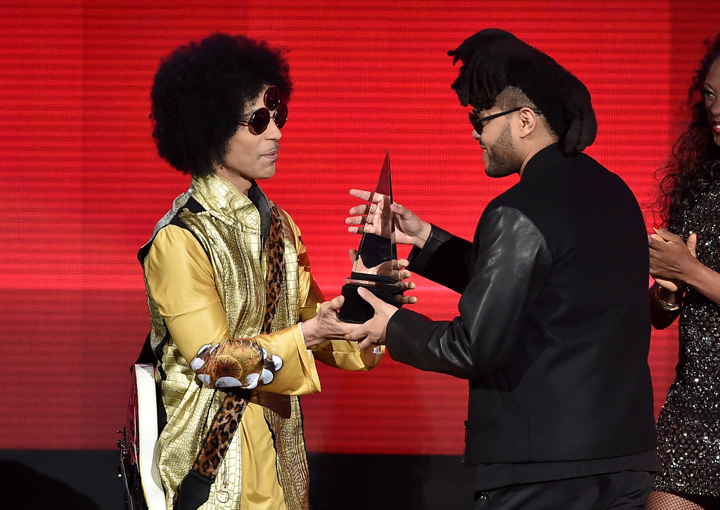 . Singer The Weeknd (R) accepts Favorite Soul/R&B Album for \'Beauty Behind the Madness\' from musician Prince onstage during the 2015 American Music Awards at Microsoft Theater on November 22, 2015 in Los Angeles, California.  (Photo by Kevin Winter/Getty Images)