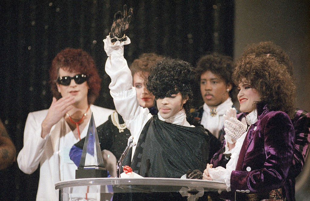 """. Pop vocalist Prince holds up a hand as he accepts an American Music Award for his single \""""When Doves Cry\"""" during presentations at the Shrine Auditorium in Los Angeles, Jan. 28, 1985. (AP Photo/Doug Pizac)"""