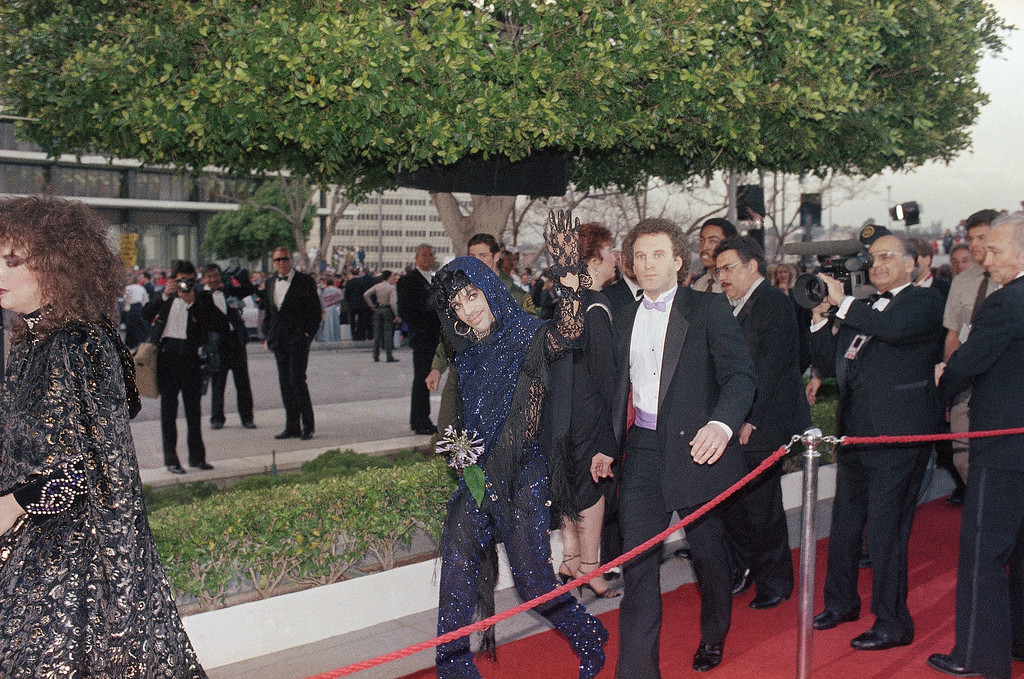. Rock singer Prince waves to the crowd upon his arrival outside the Dorothy Chandler Pavilion, site of the 57th Academy Awards, March 25, 1985 in Los Angeles. The singer won an Oscar for original score. (AP Photo/Doug Pizac)