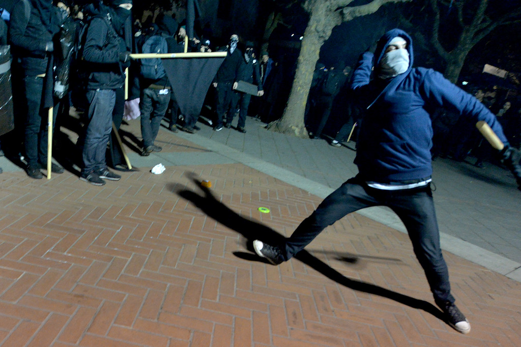 . A protester throws an object at a building during a protest against right-wing Milo Yiannopoulos who was scheduled to speak at UC Berkeley in Berkeley, Calif., on Wednesday, Feb. 1, 2017. (Doug Duran/Bay Area News Group)