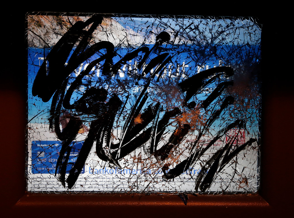 . Vandalism and graffiti are seen on a Bank of America ATM screen left by protesters against a scheduled speaking appearance by Breitbart News editor Milo Yiannopoulos on the University of California at Berkeley campus on Wednesday, Feb. 1, 2017, in Berkeley, Calif. The event was cancelled due to size of the crowd and several fires set. (AP Photo/Ben Margot)