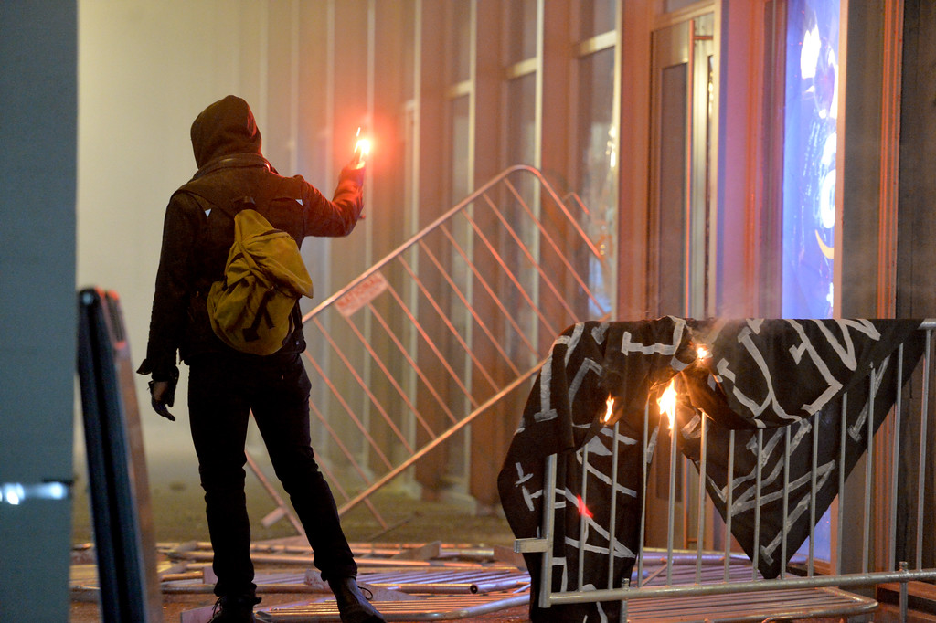 . A member of the black bloc holds up flare as they set up fires and smash windows during a protest against right-wing Milo Yiannopoulos who was scheduled to speak at UC Berkeley in Berkeley, Calif., on Wednesday, Feb. 1, 2017. (Doug Duran/Bay Area News Group)