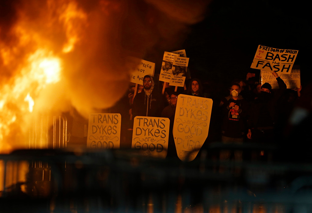 . Protestors watch a fire on Sproul Plaza during a rally against the scheduled speaking appearance by Breitbart News editor Milo Yiannopoulos on the University of California at Berkeley campus on Wednesday, Feb. 1, 2017, in Berkeley, Calif. The event was cancelled due to size of the crowd and several fires being set. (AP Photo/Ben Margot)