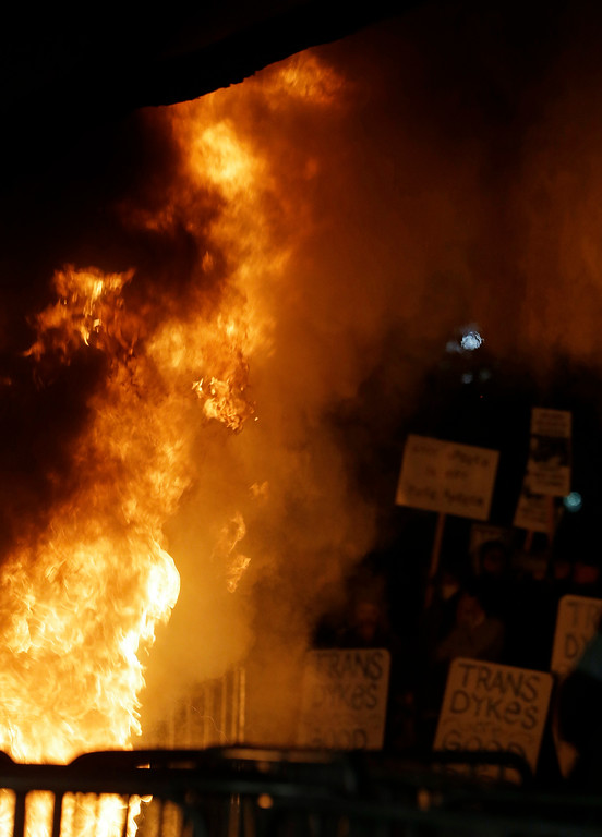 . Protesters watch a bonfire on Sproul Plaza during a rally against the scheduled speaking appearance by Breitbart News editor Milo Yiannopoulos on the University of California at Berkeley campus on Wednesday, Feb. 1, 2017, in Berkeley, Calif. The event was canceled out of safety concerns after protesters hurled smoke bombs, broke windows and started a bonfire. (AP Photo/Ben Margot)