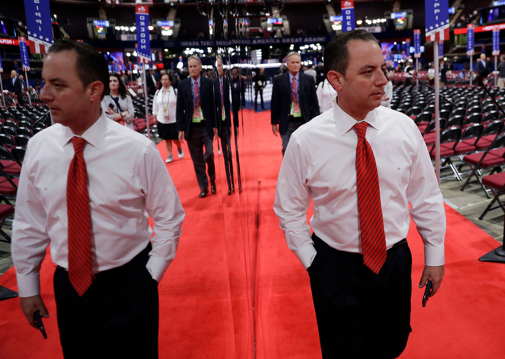 . Reince Priebus, Chairman of the Republican National Committee, is reflected in a mirror as he walks the floor before the third day session of the Republican National Convention, Wednesday, July 20, 2016, in Cleveland. (AP Photo/John Locher)