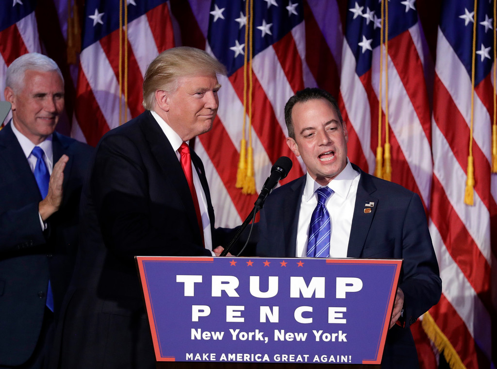 . Reince Priebus, Chair of the Republican National Committee, right, speaks as President-elect Donald Trump gives his acceptance speech during his election night rally, Wednesday, Nov. 9, 2016, in New York. (AP Photo/John Locher)