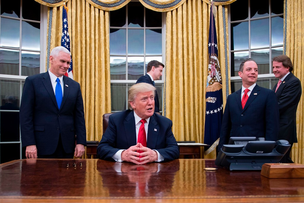 . File - US President Donald Trump (C) speaks to the press as he waits at his desk before signing conformations for General James Mattis as US Secretary of Defense and General John Kelly as US Secretary of Homeland Security, as Vice President Mike Pence (L) and White House Chief of Staff Reince Priebus (R) look on, in the Oval Office of the White House  in Washington, DC, January 20, 2017. (JIM WATSON/AFP/Getty Images)