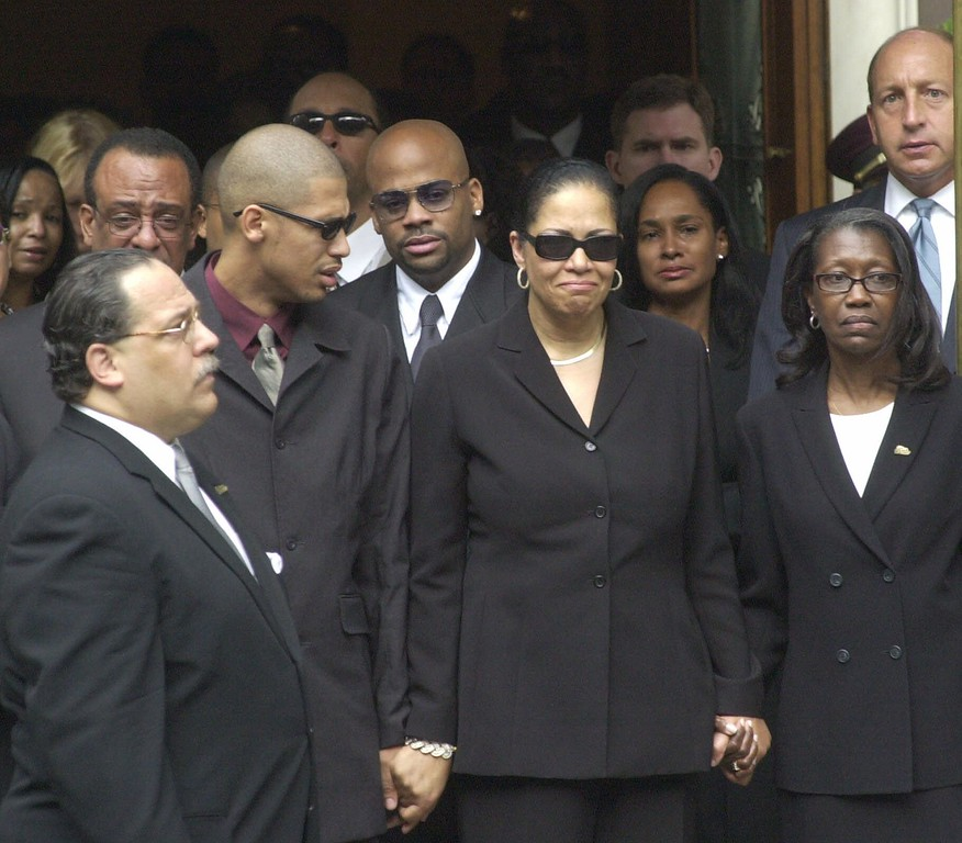 . Aaliyah\'s mother Diane Haughton, center right, holds hands with Aaliyah\'s brother Rashad, center left, as they leave the Frank E. Campbell Funeral Chapel on their way to the singer\'s funeral at the St. Ignatius Loyola Church in New York Friday, Aug. 31, 2001. Aaliyah\'s boyfriend Damon Dash follows her mother and brother at center. (AP Photo/Stephen Chernin)