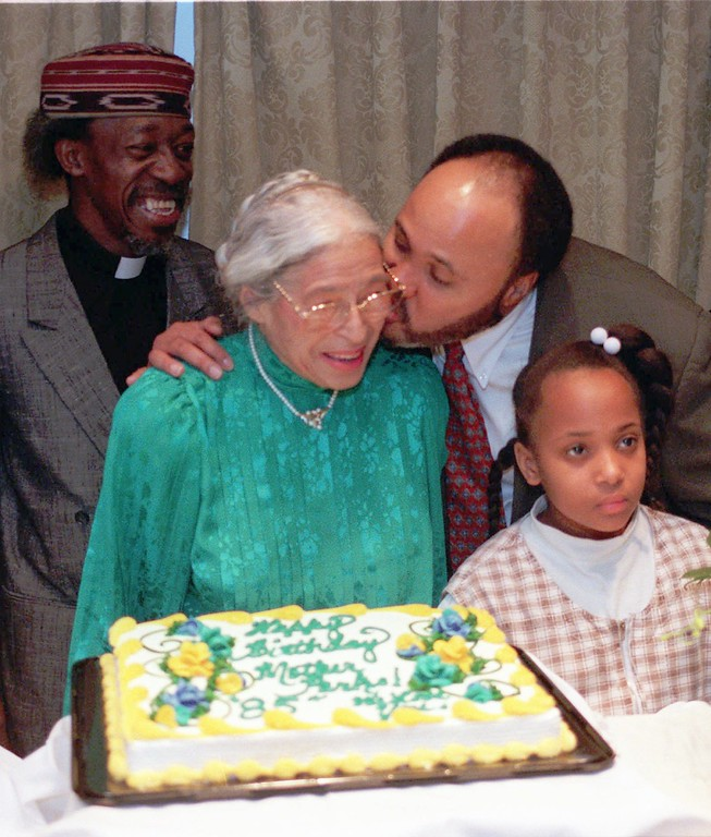 . Martin Luther King III kisses civil rights activist Rosa Parks during her 85th birthday celebration in Atlanta on Wednesday, Feb. 4, 1998 as the Rev. Randall Osborne, left, and Ramia Finley look on. (AP Photo/Alan Mothner)