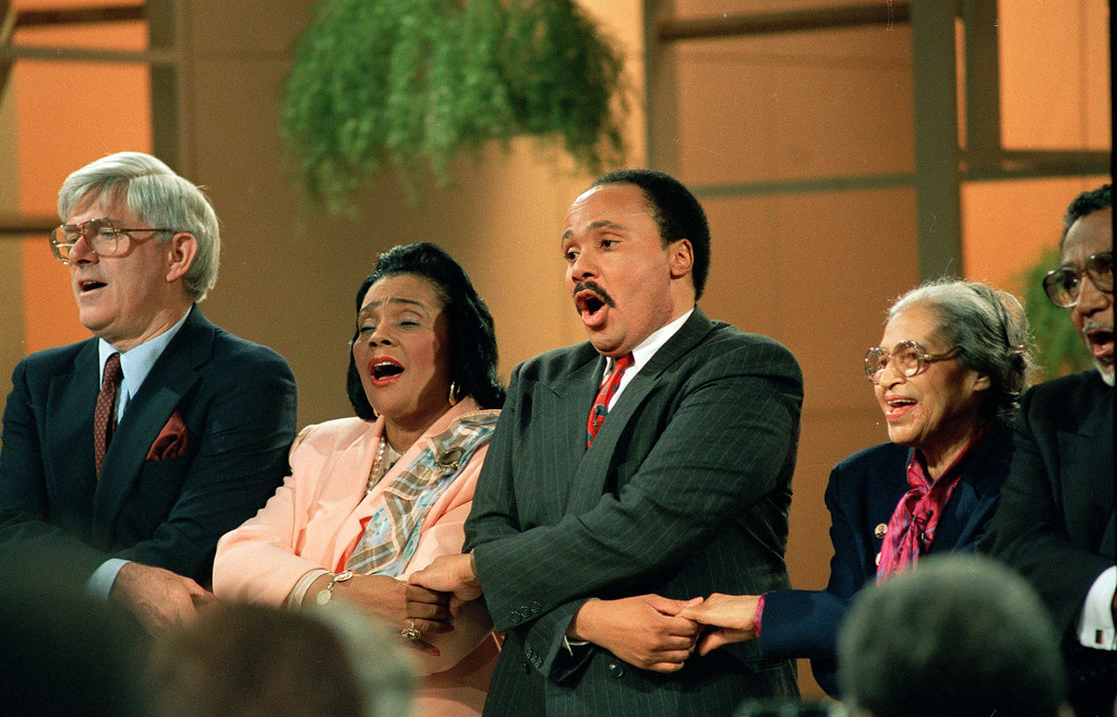 ". Television talk show host Phil Donahue, left, joins hands and sings with civil rights leaders Coretta Scott King, Martin Luther King III, and Rosa Parks, who sparked the Montgomery, Ala. bus boycott by refusing to give her seat to a white man and sitting in the back of the bus, on the set of the ""Donahue\"" show, April 1, 1988.  (AP Photo/Mark Lennihan)"