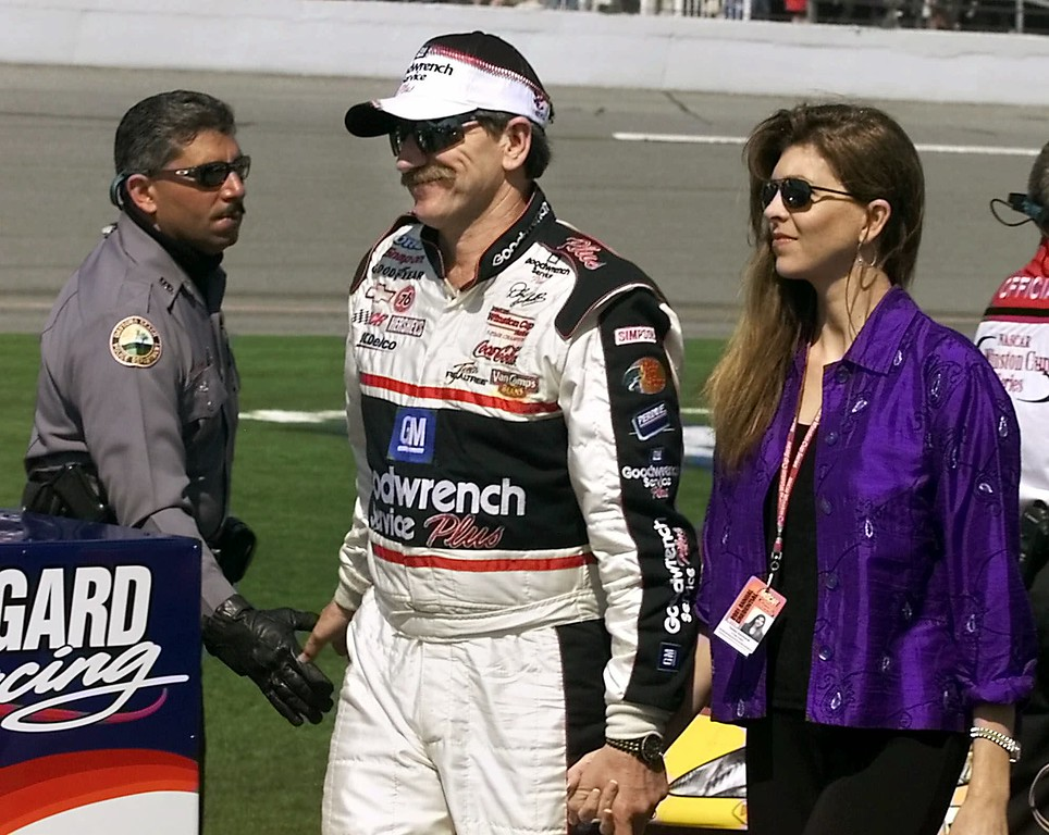 . FILE - This Feb. 18, 2001, file photo shows NASCAR driver Dale Earnhardt Sr., center, walking down pit row holding the hand of his wife, Teresa, right, and shaking the hand of a Daytona Beach police officer just prior to the start of the Daytona 500 auto race,  in Daytona Beach, Fla. Thursday, Feb. 18, 2016 marks the 15th anniversary of Earnhardt\'s fatal crash at Daytona. (AP Photo/Bruce Ackerman, File)