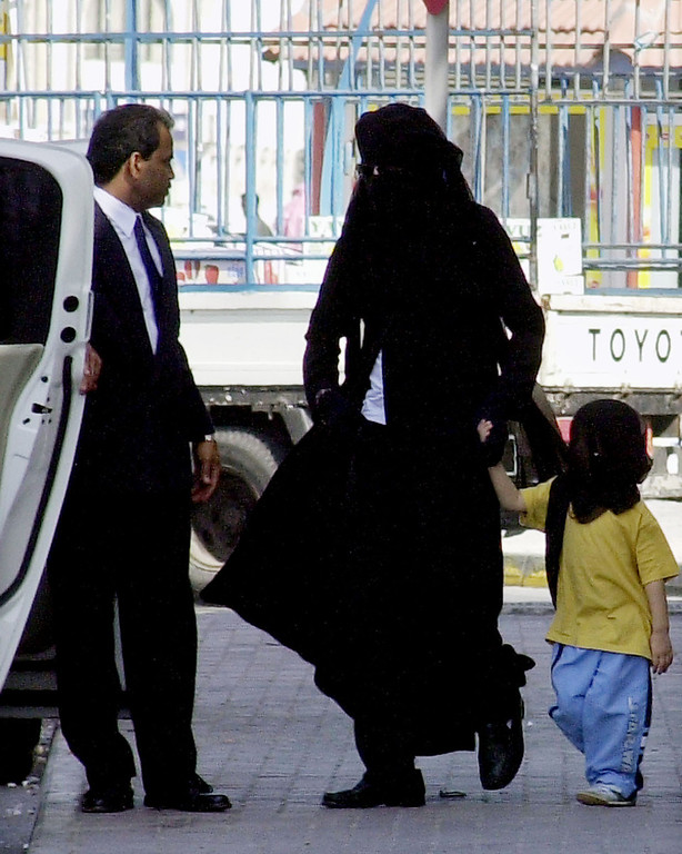 . Michael Jackson, center, wears an abaya, the traditional Arabic women\'s veil and all-covering gown, and holds the hand of one of his children, Prince Michael II, also veiled, as they walk toward their car Wednesday, Jan. 25, 2006, behind a shopping mall, in Manama, Bahrain.   (AP Photo/Hasan Jamali)
