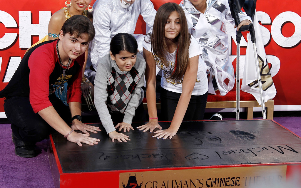 ". Paris, right, Prince, left, and Blanket Jackson put their hands in cement during the hand and footprint ceremony honoring their father, musician Michael Jackson, in front of Grauman\'s Chinese Theatre in Los Angeles, Thursday, Jan. 26, 2012. The ceremony was held to celebrate the ""Michael Jackson The Immortal World Tour\"" by Cirque du Soleil.  (AP Photo/Matt Sayles)"