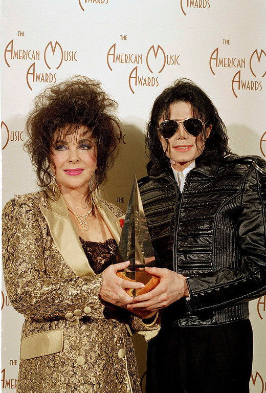 . Pop singer Michael Jackson, right,  holds his award while posing with actress Elizabeth Taylor at the 20th American Music Awards held at the Shrine Auditorium in Los Angeles, Calif., January 25, 1993.  (AP Photo/Mark Terrill)