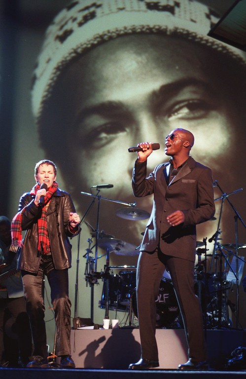 ". British pop singers Seal, right, and Annie Lennox rehearse their duet of Marvin Gaye\'s soul classic ""What\'s Goin\' On\"" in front of a background portrait of the late singer, Tuesday, Feb. 27, 1996, in preparation for the 38th Annual Grammy Awards at the Shrine Auditorium in Los Angeles. (AP Photo/Chris Pizzello)"