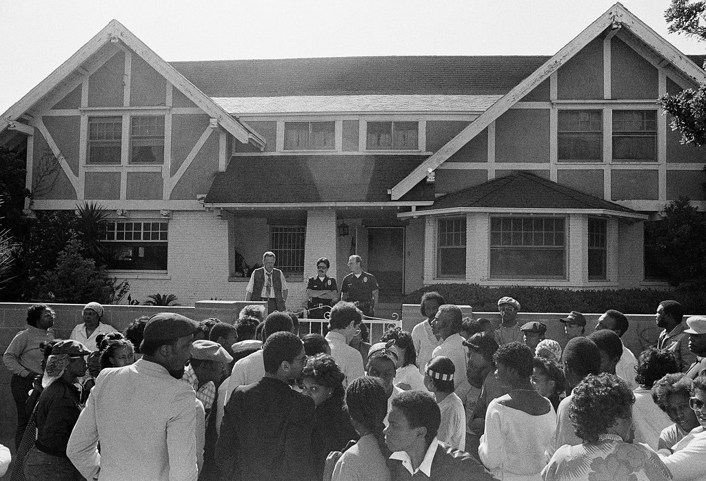 . Los Angeles police officers, neighbors and fans stand in front of the home of singer Marvin Gaye\'s parent\'s on April 1, 1984 in Los Angeles where he was shot and killed Sunday afternoon near the downtown section of Los Angeles. Gaye\'s father Marvin Gaye senior is being questioned by police in connection with the shooting. (AP Photo/Michael Tweed)