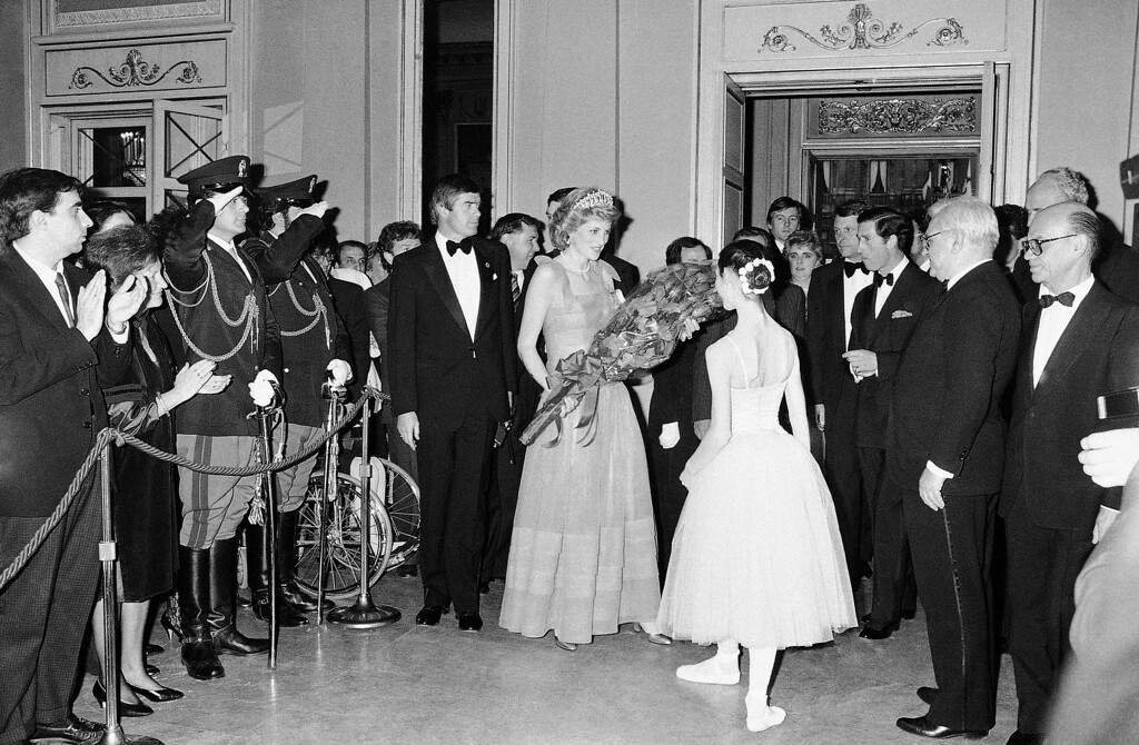 . Princess Diana receives a bouquet of flowers from a ballerina at the entrance hall of the Scala Opera House of Milan, Italy on Saturday, April 20, 1985. (AP Photo/Foggia)
