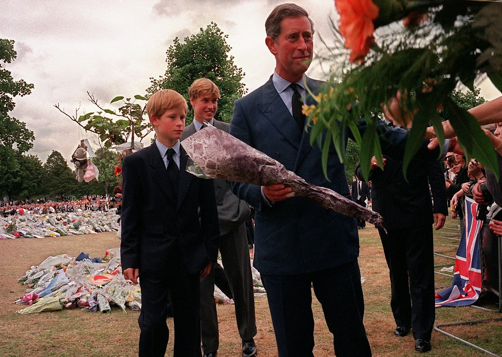 . Prince Charles, right, accepts some flowers from a well-wisher after he and his sons Prince William, and Prince Harry, left, arrived at Kensington Palace to view some of the flowers and mementos left in memory of their mother Princess Diana in London, Friday, Sept. 5, 1997. (AP Photo/David Brauchli)