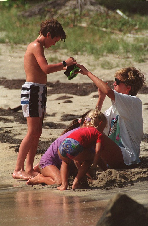 . Princess Diana of Great Britain hands son William his diving mask after she adjusts the strap at Banana Bay Beach in St. Kitts, Monday, Jan. 4, 1993. (AP PHOTO/Richard Drew)