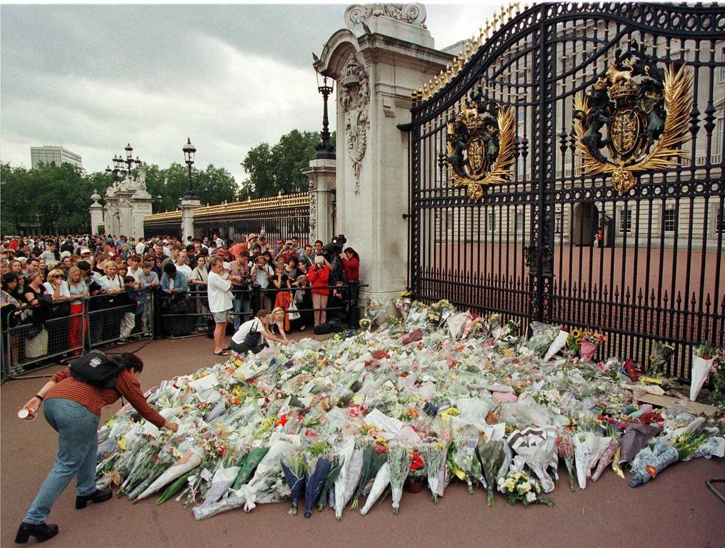 . A mourner places more flowers on the pile outside the gates of Buckingham Palace in London, Sunday Aug. 31, 1997, following the death of Diana, Princess of Wales. The Princess, along with her companion Dodi Fayed, and a driver, were killed in a car crash in Paris, earlier in the day. (AP Photo/Adrian Dennis)