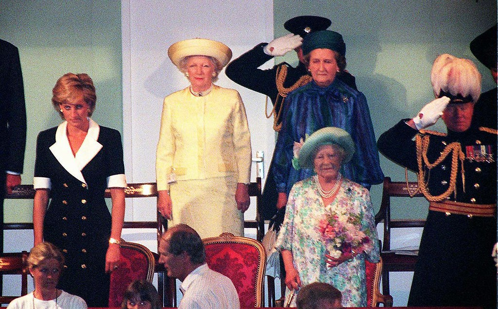. Britain\'s Queen Mother, second from right, holding flowers and The Princess of Wales, left, are positioned one seat apart as they stand for the National Anthem, during the Royal Tournament at London\'s Earls Court, Thursday July 11, 1996 before the start of a musical military tournament. (AP Photo/John Stillwell)